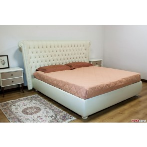 Cream leather bed with buttoned details similar to a Chesterfield one